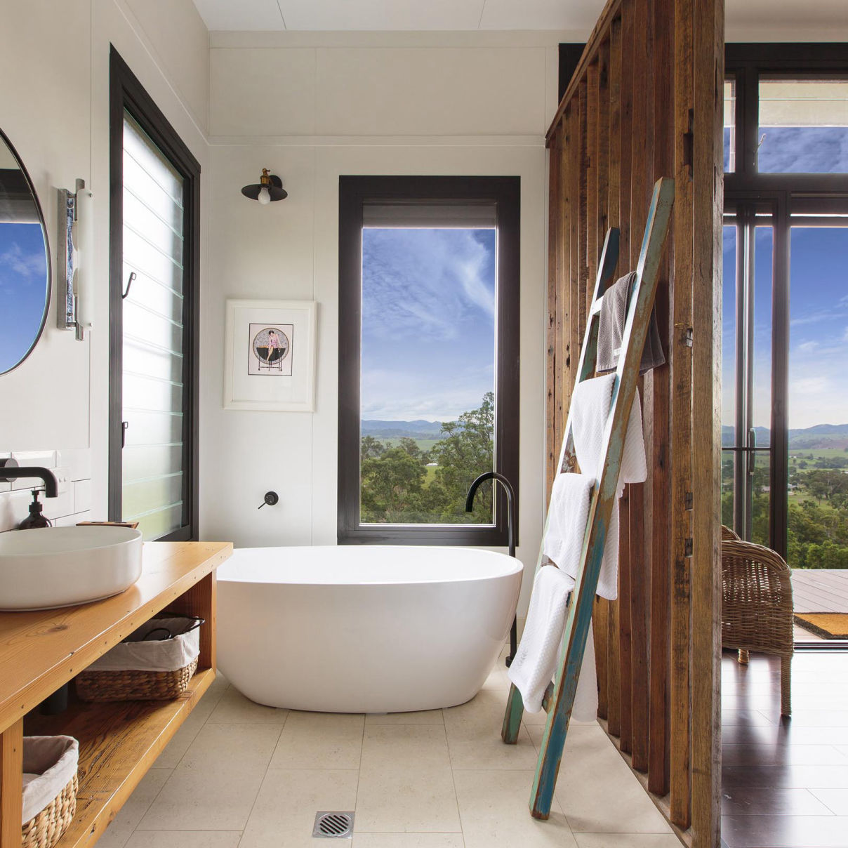 This MAAP House bathroom contains a freestanding bathtub with feature timber screen and recycled towel ladder